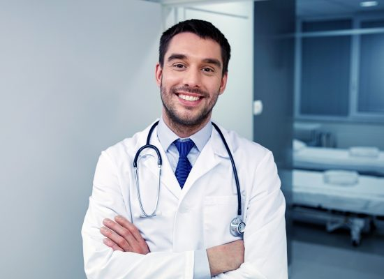 smiling-doctor-with-stethoscope-at-hospital-PVS8FJU